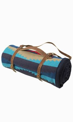 Tropical colors meet tribal graphics in this blanket inspired by Lahaina in Maui. Complete with a leather carrier, the design's blue and turquoise waves capture the island's beach paradise.