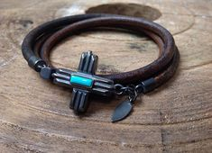 Mens bracelet, wraps 3 times. This native inspired wrap features a gorgeous hand made sterling silver clasp in a southwestern cross design with natural Sleeping Beauty turquoise accent and a soft 5 mm natural round antique Brown leather cord. This distinctive bracelet wraps around the