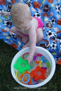 Teething toys in water bucket = babies first sensory bin.