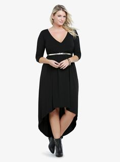 This black knit dress has a sexy faux wrap neckline and a must-wear hi-lo silhouette. Includes a gold tone skinny belt.
