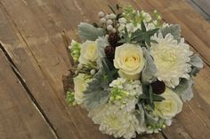 Wintery white bridal bouquet with roses, chrysanthemums, baby's breath, stocks, pine corns, brunia, eucalyptus and dusty miller. Designed by Forget-Me-Not Flowers