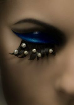 heavy blue eye makeup with pearl lashes