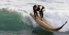 "Peruvian surfer Sofia Mulanovich rides a wave on top of a ""reed horse"", an ancient boat still used in northern Peru, at San Bartolo beach in Lima, Peru. May 27, 2010"