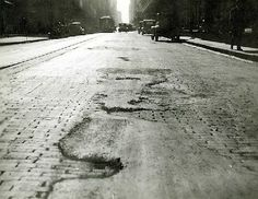 Deteriorating woodblocked road surface in Castlereagh Street, between Goulburn and Liverpool Streets, 1932. The holes have been spot filled with bitumen.
