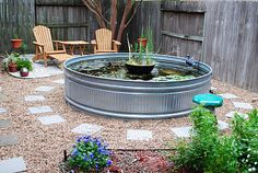 Use of a large stock tank as a backyard pond or water feature ... such a great idea.