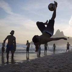 """A beachgoer bicycle kicks the ball during a game of """"altinho"""" along the shore of Ipanema Beach in Rio de Janeiro Brazil on July 13 2015. Altinho is a popular local game that is played with a soccer ball on the beach. The goal is not to let the ball drop but passing to other players while keeping it airborne. Photograph by Leo Correa of @ap.images. by time"""