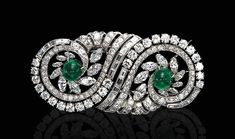 AN ART DECO DIAMOND AND EMERALD DOUBLE CLIP BROOCH - Each designed as a marquise, baguette and old European-cut diamond scroll, centering upon a cabochon emerald, mounted in platinum, circa 1930.
