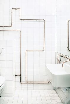 Clever bathroom pipe design on white tile