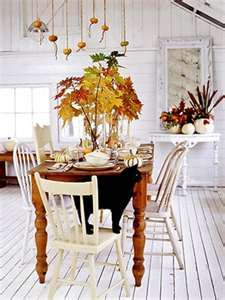 whitewashed wood floors, vaulted barn like ceiling all whitewashed, mixed vintage & painted chairs, white painted console with large mirror, fall foilage, lovely & welcoming
