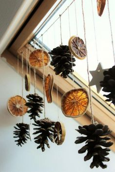 dried orange slices, several pine cones and star shapes, tied to a string and hanging from a ceiling window with wooden window pane #christmasgifts