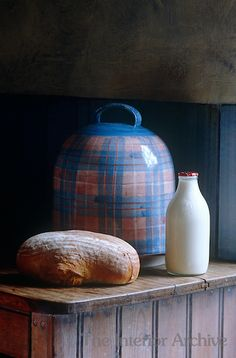 A blue-and-pink check ceramic bread bin (Anta) on top of an antique cupboard in the kitchen of a Scottish-themed London town house
