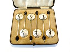 1930s coffee spoon set with a dancing lady illustration. Offered by Connie Speight at Alfies Antique Market.
