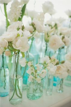 White flowers in mismatched aqua bottles