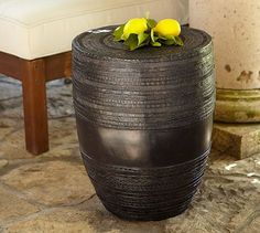 "Metal Drum Accent Table at Pottery Barn. Rain drums, named for the sound they make when tapped by raindrops, have existed in Asian cultures for thousands of years. Our cast-aluminum version features a traditional relief pattern.  Made of aluminum with an antique-bronze finish.  Crafted in Thailand and designed with smooth concentric patterns.  For use indoors or out.  16"" diameter, 20"" high  Catalog / Internet only."