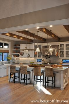 While this kitchen is big, it seems cozy to me. I love the island, the beams in the ceilings, the wood floors, and the recessed and hanging lighting.