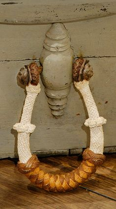 A becket, or rope handle, attached to one side of a grey, sailor's sea chest. ~ I thought these were bucket handles, lol