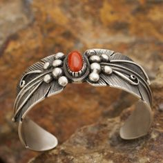 """This beautiful Sterling Silver Cuff Bracelet is hand crafted by Navajo Artist BRD and incorporates a feather design with a Red Coral accent. Cuff Size: Medium-- 6 1/4"""" Wrist Width:1"""" If this item is n"""