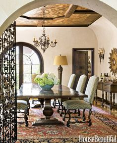 """The dining room is bathed in a blushed peach that gives the room a twilight aura """"and really flatters the complexion,"""" Callaway says. Woodwork is painted in faux grained walnut. Country Trestle table, Emanuel Morez. Barcelona dining chairs by Panache Designs, covered in a Kravet fabric. Antique Pakistani rug.   - HouseBeautiful.com"""