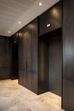 An upmarket look was required for this elevator lobby so dark, bronze-tones were specified which complement the travertine flooring. Fabrication, V-Grooving and folding of stainless steel by John Desmond Ltd. @johndesmondltd Lobby Interior, Interior Architecture, Elevator Lobby Design, Lift Design, Travertine Floors, Wood Cladding, Architrave, Modern Design, Case Study