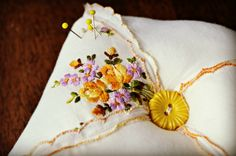 Sweet little pin cushion made from an antique handkerchief and vintage button, which it is as cute as...