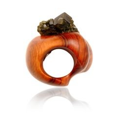 This ring is made of wood and some kind of jewel. It shows clearly the pattern of wood and has smooth texture like shiny wooden table. There is small black jewels that are attached at the top. Ring is not perfectly round but gets bigger as it goes to the top.