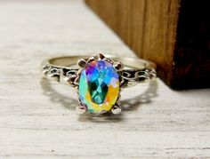 A mystic rainbow topaz set in a fancy sterling silver setting that has a Victorian look. The band has been oxidized to bring out the beautiful filigree design that tops off with this gorgeous stone. M