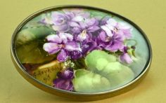 """A Hand Painted Porcelain And Metal Belt Buckle Depicting African Violets - Signed """"G Leykaul"""" And Dated """"98"""", Possibly 1898, c. Early 20th Century"""