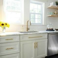 White and gold kitchen features white shaker cabinets adorned with brass pulls p. White and gold kitchen features white shaker cabinets adorned with brass pulls paired with calcutta White Shaker Cabinets, White Kitchen Cabinets, Kitchen Redo, New Kitchen, Kitchen Dining, Gold Kitchen Hardware, Kitchen White, Gold Kitchen Faucet, Kitchen Ideas