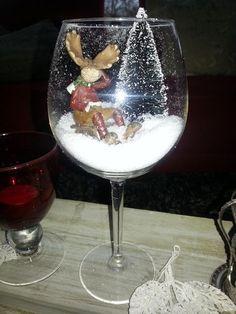 Leuke kerstdecoratie in je huis. Rendier op een slee in de sneeuw in een groot wijnglas.