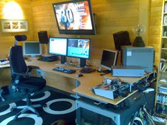 Home editing studio idea. Like the multiple monitors + hanging TV. Too many wires in sight however.