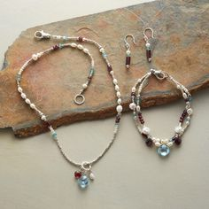 """The passionate glow of red garnet and the frosty cool of sterling silver, apatite and pearls join a glittering faceted blue topaz in handcrafted jewelry that makes the event. USA. Necklace 17""""L, bracelet 7-1/2""""L, earrings 1-3/8""""L. $238."""