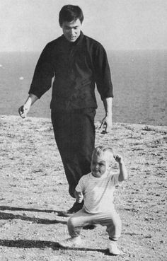 Bruce Lee with a very fierce looking Brandon Lee on the beach.