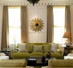 White walls, light tan drapes, bamboo blinds, white glossy table lamps, green couch, golds.
