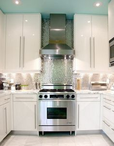 white glossy cabinets, shimmery tile and a blue ceiling