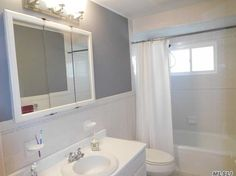 Small White bathroom, white tile, white fixtures gray painted walls, white cabinet.