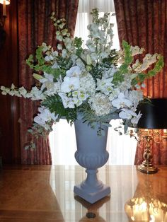 A lush arrangement featuring white phalaenopsis orchids, white larkspur, white hydrangea and bells of Ireland.  To view our entire selection please visit us at www.starflor.com #flowers #events #eventdecor