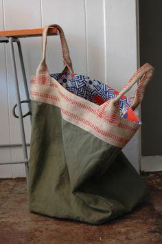 Esta bolsa comenzó su vida como una bolsa de lona de la guerra mundial 2 de 1945 que perteneció a un soldado. El exterior está compuesto de la bolsa de lona y 3 frontera de yute con asas de yute. El interior está forrado con este asombroso Andy Warhol estilo vintage tela. La bolsa puede ser revertida y ha hecho un bolsillo ejército verde del mismo material como el exterior. Imperfecciones en la bolsa de tela de lana basta de esperar. Esto es una buena bolsa.
