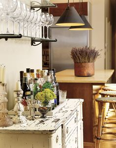 A painted bureau serves as a bar handy to the kitchen.