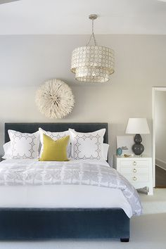 Fabulous bedroom features a tiered capiz chandelier, Smoked Capiz Two-Tier Pendant, over a white juju hat situated…