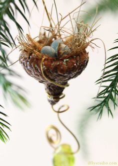 You have just discovered a one-of-a-kind and very unique art piece.    Our acorn shell birds nests are made inside a real acorn cap using woodland grasses and moss and perfect little bead eggs.    Each nest is created using a copper or brass hanging wire and beads or charms as embellishments. As you can see, each nest is quite unique. There may be some which are alike - but never the same.    Some nests have a touch of glitter on the acorn shell - giving it a charming fairy-like quality…