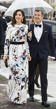 Crown Princess Mary, looked chic as she stepped out in a floor length white number stamped with a blue and red floral design. She paired her look with a pair of simple silver pumps, a stylish black clutch and eye-popping chandelier diamond earrings. Crown Prince Frederik of Denmark also looked handsome in a tailored navy suit and bowtie.