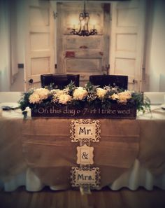 Head table backdrop of vintage doors and chandelier with burlap table overlays and custom made and stenciled flower box
