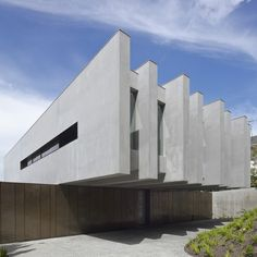 A house in Melbourne where cantilevering concrete slabs appear to balance on top of a bronze garden wall.