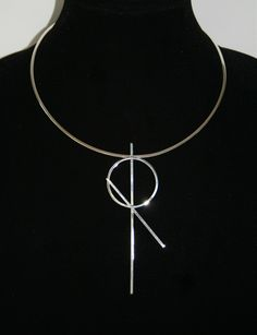 Visibly Interesting: Minimalist necklace featuring a modernist inspired XO pendant in solid Sterling Silver on a hand sculpted neckring.