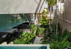 """O paisagismo exuberante assinado por Raul Pereira quebra a rigidez do concreto estendendo-se por todo o comprimento do terreno até a rua. Ao fundo, a escada metálica passa entre as """"pernas"""" do pilar duplo de sustentação. A Casa de Fim de Semana foi projetada pelo escritório SPBR Arquitetos"""
