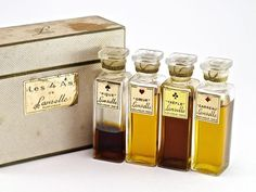 1940s Lanselle Les 4 As (The 4 Aces) perfume sampler, glass bottles and stoppers, sealed, each label a card suit image and name, box (worn). 2 3/8 in.