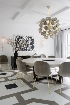 Contemporary white, gray, and black dining room boasts a large, round, gray dining table seating gray velvet dining chairs with gold legs on a white and gray painted wood floor. Large Round Dining Table, Round Dining Room Sets, Grey Dining Tables, Large Dining Rooms, Dining Room Modern, Grey Dining Room Chairs, Black Round Table, Round Wood Dining Table, Dining Chair Set