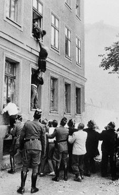 People escape through building windows to West Germany as the Berlin Wall is being built. August 1961.