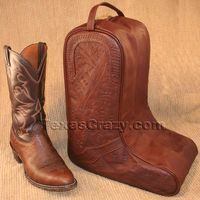 Travel Texas style with these western cowboy boot bags, one of the tooled leather bags from our Texas Luggage collection.Classically styled for the western lifestyle, the bag includes sturdy top padded handles, tooled leather, long dual zippers that wrap under the boot bag, and two easy clean vinyl-lined boot compartments. A center wall protects and separates the cowboy boots from each other. The bag measures 14 inches L x 17 H x 8 W and fits most cowboy boots (the boots featured are size 12…
