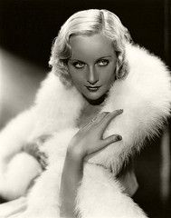 CAROLE LOMBARD.  The best accessory for setting off your suntan is a always white fur stole, of course.